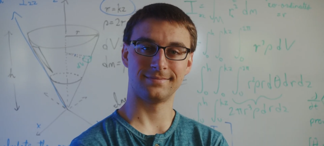 a student faces us as he stands in front of a whiteboard covered with equations