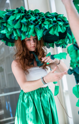 a student performance artist in a huge green hat and costume
