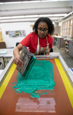 a student using screen printing equipment
