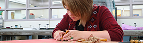 Student works on a wood carving