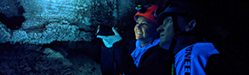 Students look at cave organisms with a blue light