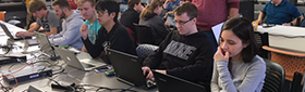 Students compete over their laptops for cyber security