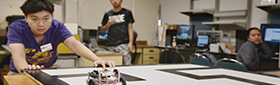 Robotics students review and test their work