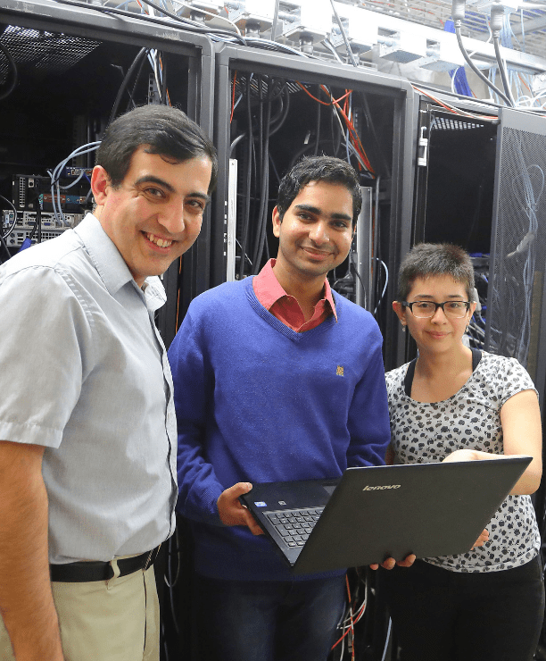 three people gather together in the ohysics server room at UNI