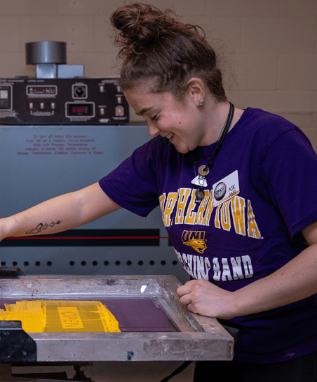 a student smiles as they work at a machine used for printing