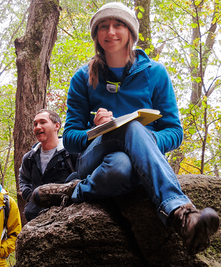 a student with a notebook sits atop a log in the woods, surrounded by other students