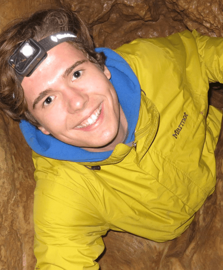 a student smiles as they pull themselves through a hole in a cave wall