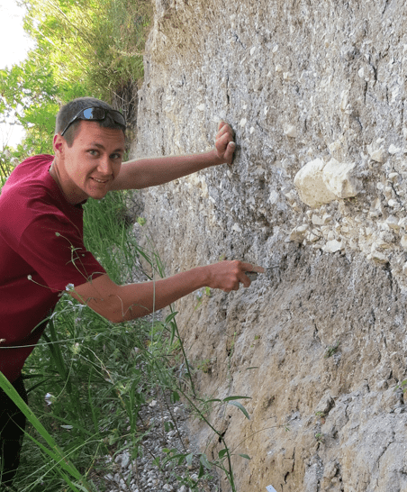 a student examines a rocky wall
