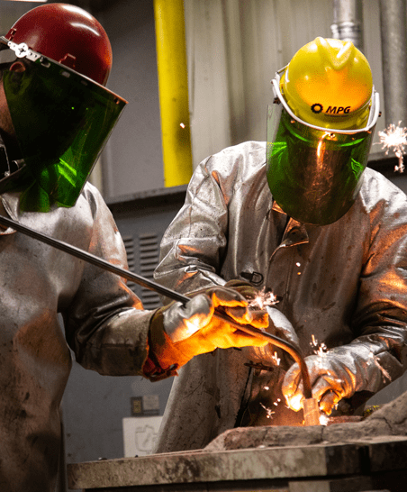 two students in protective gear work with hot metal