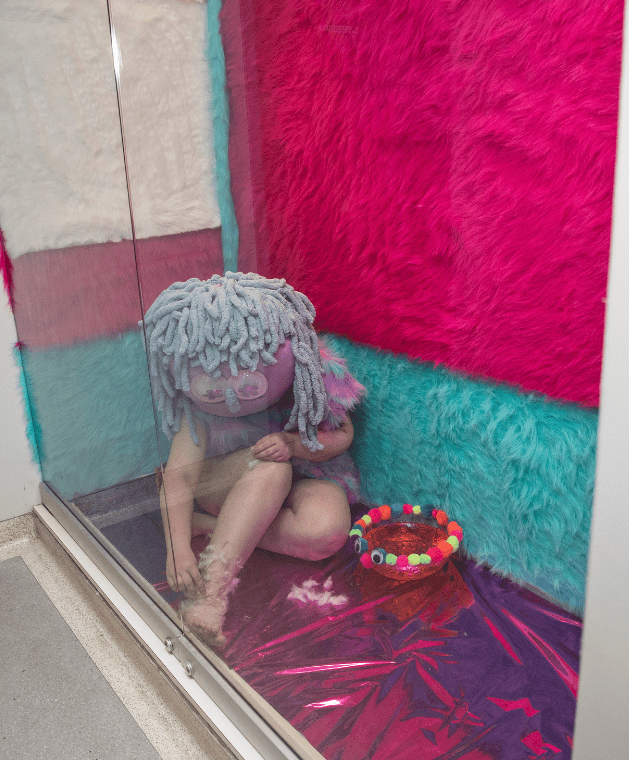 a student performance artist in a costume crouches in a decorated display case