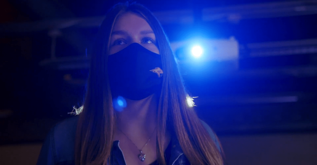 a student wearing a mask illuminated from behind by blue light