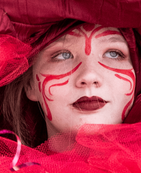 An art student dressed in a brilliant red costume with red face makeup and lips looks off into the distance