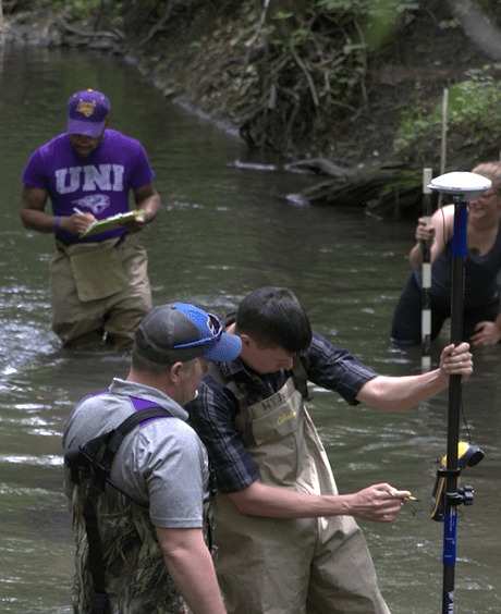 students testing water in a creek