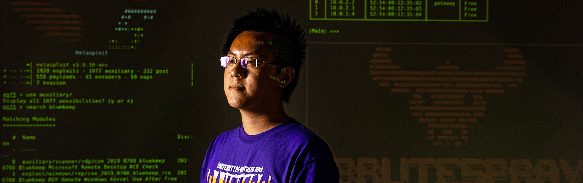 computer science student in front of a wall of code