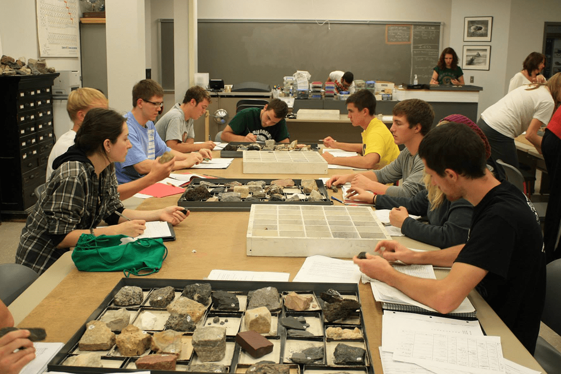 students at a table looking at fossils