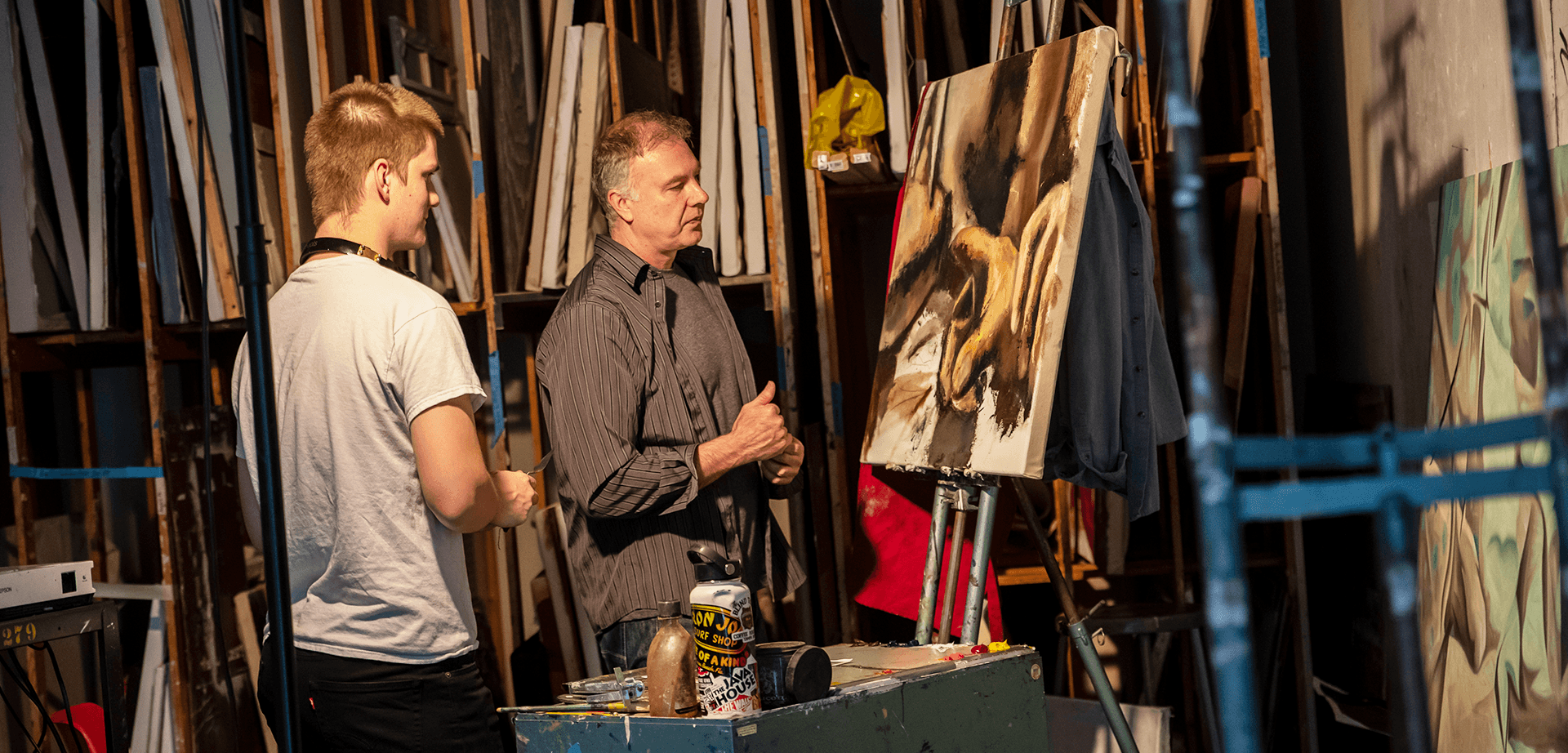 student and instructor inspecting a painting on easel