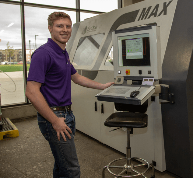 a student stands next to a large 3D printer in the UNI Metal Casting Center