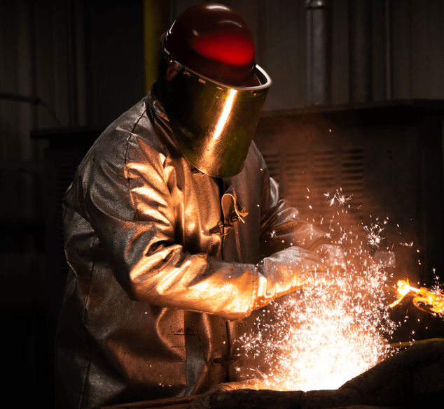 a student in protective gears works with hot metal as sparks fly
