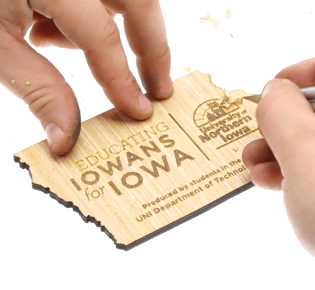 a student uses an exacto knife to clean the edges of a wooden cutout of Iowa