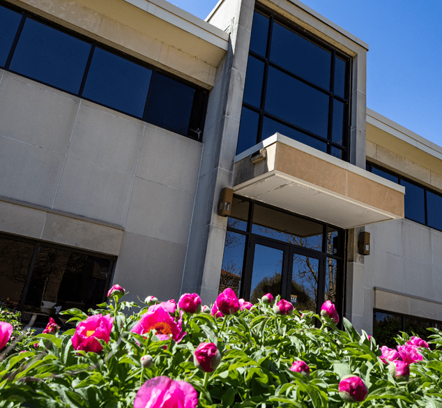 latham hall shown behind some blooming pink flowers