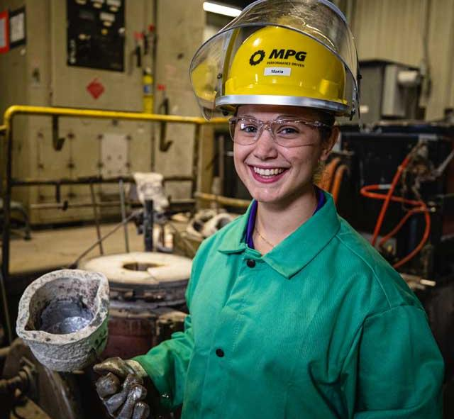 a student worker in a hard hat smiles for the camera while holding up a cast